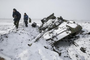 Members of the separatist self-proclaimed Donetsk People's Republic army collect parts of a destroyed Ukrainian army tank in the town of Vuhlehirsk, west of Debaltseve