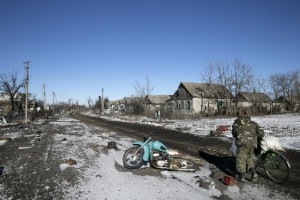 A man pushes a bicycle along buildings damaged by fighting in the village of Nikishine