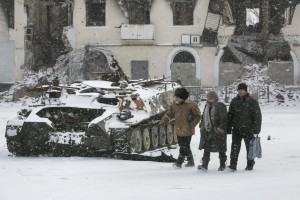 Locals walk past a destroyed Ukrainian army armoured personnel carrier in the town of Vuhlehirsk, west of Debaltseve