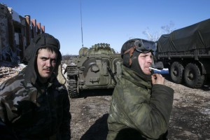 Fighters with the separatist self-proclaimed Donetsk People's Republic smoke near an armoured personnel carrier in the village of Nikishine